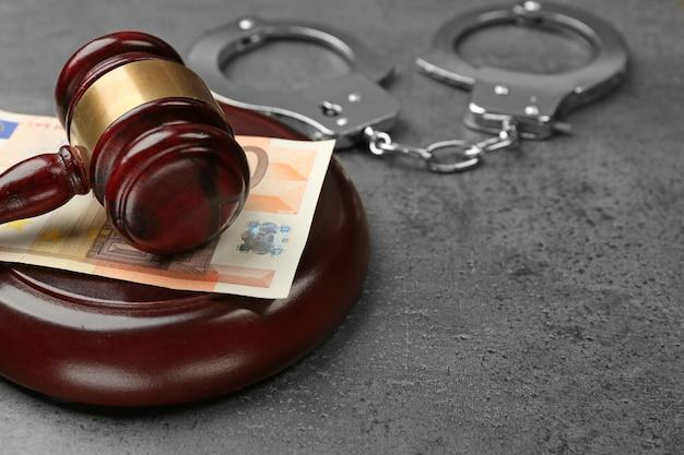 Молоток закона с евро и наручниками на сером столе, крупным планом