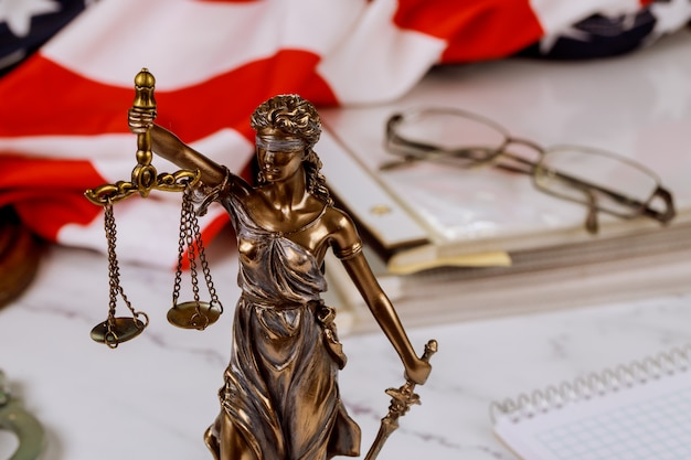 Law judge desk with lady justice statue on of paper files documents stacked with us flag