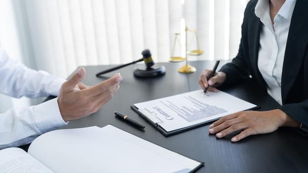 法律、てんびん座の体重計、テーブルの上のハンマー、2人の弁護士が契約書、法律問題の決定、オープンハンドについて話し合っています。