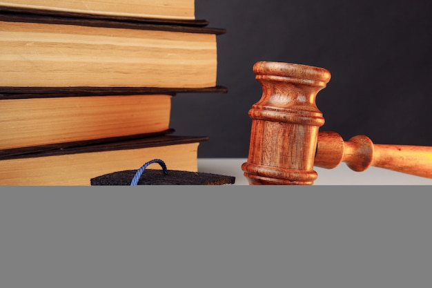 졸업 모자와 나무 망치 클로즈업이 있는 법률 또는 교육 개념 책
