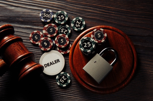 Law and rules for online gambling concept, judge gavel and padlock with playng cards and chips on wooden table close-up