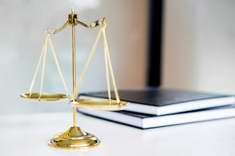 Law scales or golden weight and legals books on table. Symbol of justice