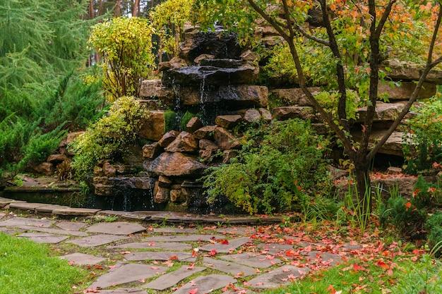 Газон среди декоративных хвойных кустарников с дорожкой и искусственной скалой с водопадом