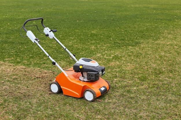 フィールドまたは庭の表面の緑の草の上の芝刈り機