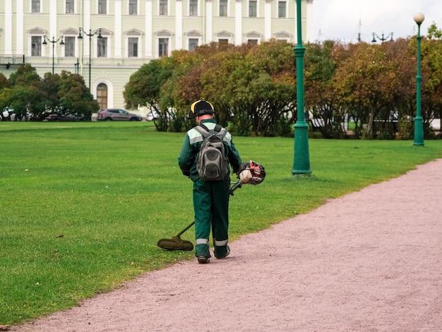 Газонокосилка сзади за работой. городской сервис, уход за городским газоном в парке.