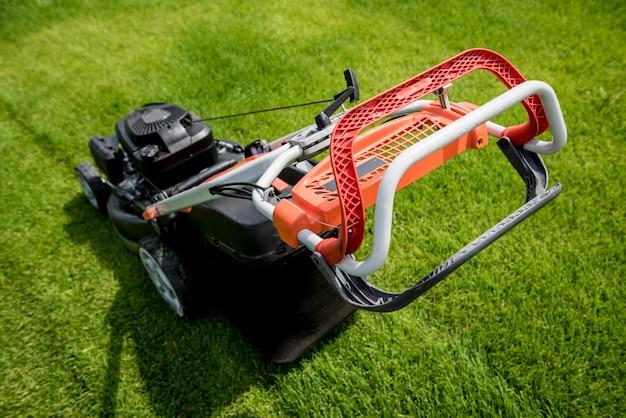 Lawn mower on green grass. summer garden