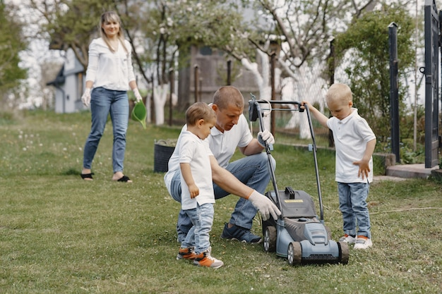 Газонокосилка человек работает на заднем дворе с сыновьями