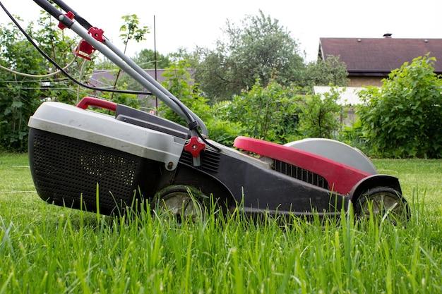 녹색 풀밭에 잔디 깎는 기계. 원예 및 조경 개념입니다.