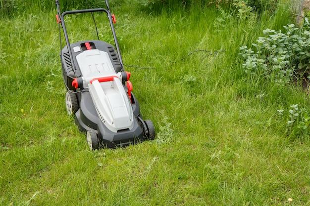 봄 정원에서 푸른 잔디에 잔디 깎는 기계. 잔디 깎는 기계. 정원사 관리 작업 도구를 깎습니다.