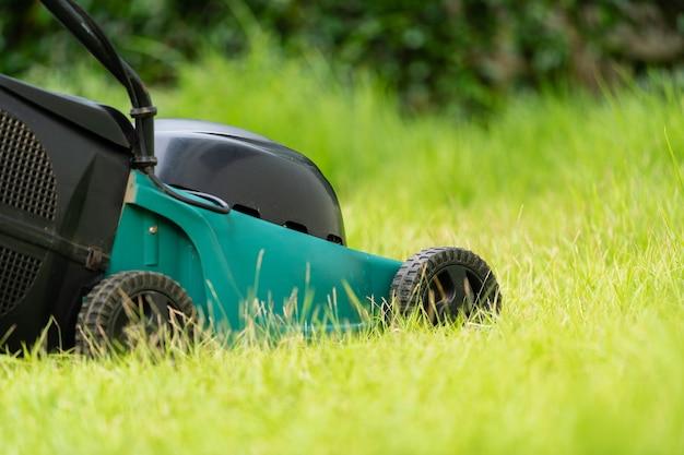 自宅の緑の芝生の芝刈り機