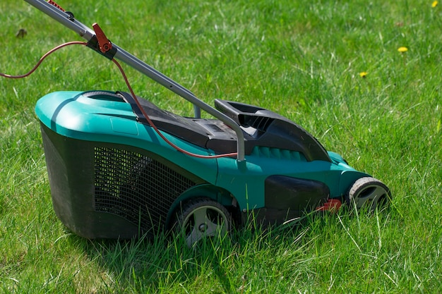 Lawn mower standing on green lawn