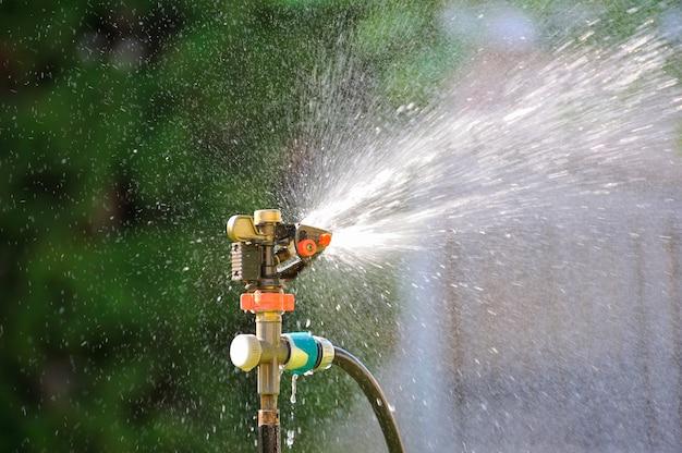 緑の草の上に水を噴霧する芝生のスプリンクラー。灌漑システム。バックライト