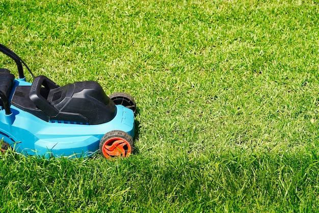 緑の草の芝生の切断をトリミングする芝刈り機電気機械