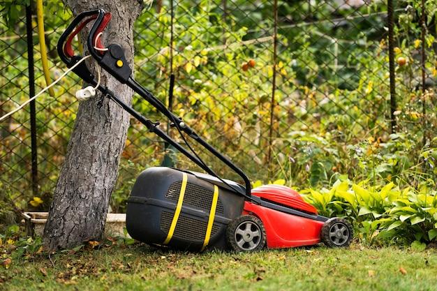 화창한 날 야외에서 푸른 잔디에 잔디 깍는 기계