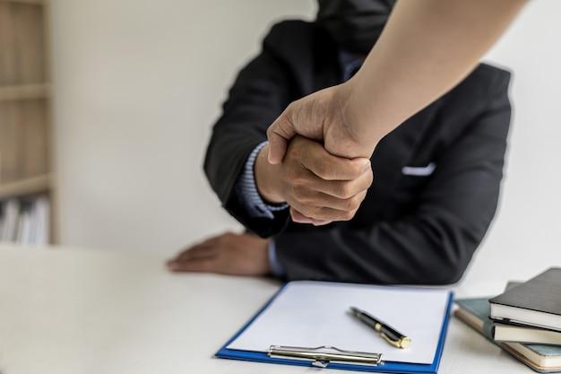 弁護士とクライアントは握手し、詐欺事件でクライアントに雇われた弁護士が公正かつ正しい方法で訴訟を起こした後、クライアントが訴訟に勝ちます。詐欺訴訟の概念。