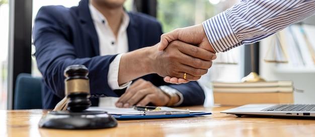Адвокат и клиент обмениваются рукопожатием, подписывают иск за клиента, в котором клиент подал иск против сотрудника компании, совершающей мошенничество. понятие судебного консультирования.