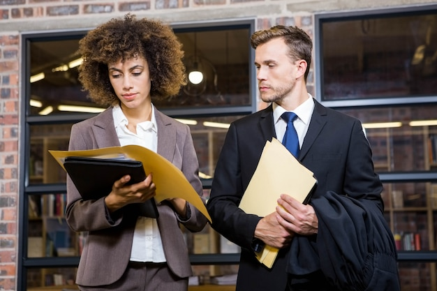 Lawyer and businesswoman looking at documents in office