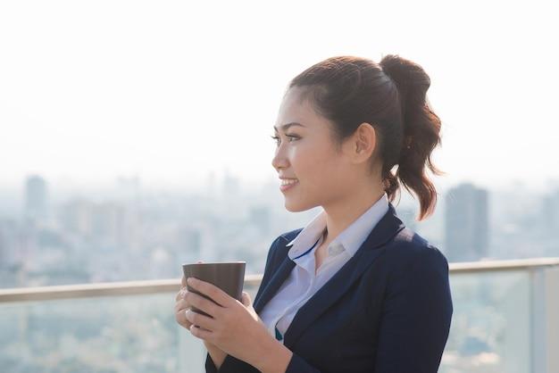 Профессиональная бизнесвумен юрист гуляет на открытом воздухе, пьет кофе из одноразового бумажного стаканчика. многорасовый азиатский / кавказский предприниматель улыбается