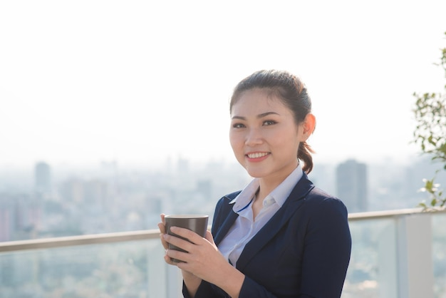 Lawyer businesswoman professional walking outdoors drinking coffee from disposable paper cup. multiracial asian / caucasian businesswoman smiling