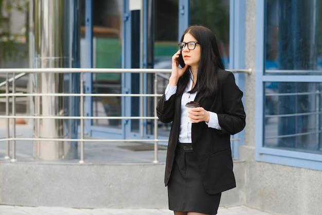 Профессиональная коммерсантка юриста гуляет на открытом воздухе разговаривает на сотовом смартфоне, пьющем кофе из одноразового бумажного стаканчика.