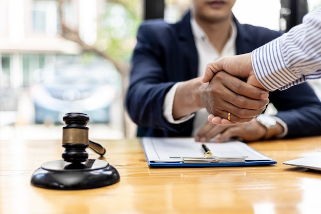Lawyer and client shake hands, sign a lawsuit for the client, in which the client has filed a lawsuit against an employee of a company that commits fraud. the concept of litigation counseling.