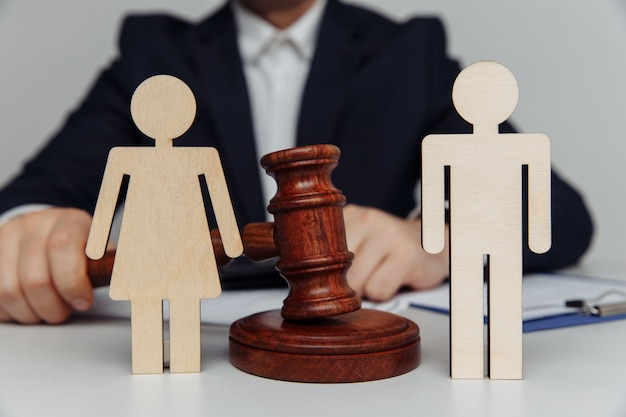 Lawyer or counselor holds gavel behind of figures of young family divorce or separation concept