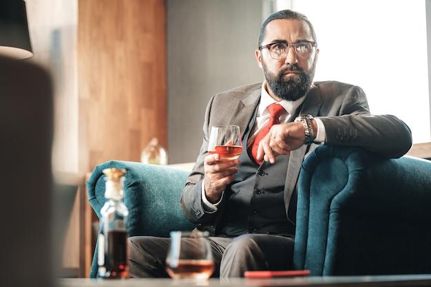 弁護士が飲んでいます。快適な肘掛け椅子に座ってアルコールを飲み、葉巻を吸うひげを生やした黒髪の弁護士