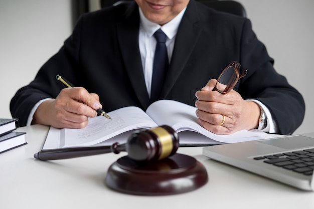 Lawyer hand writes the document in court (justice, law) with sounding block