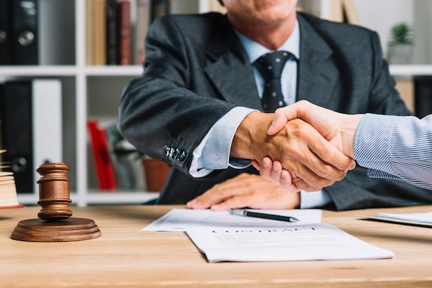 Lawyer and his client shaking hands together over the desk