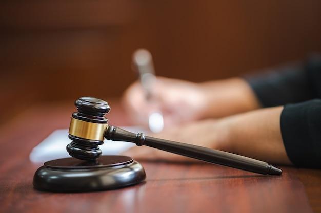 법정에서 사건을 작성하기 위해 펜을 들고 있는 변호사