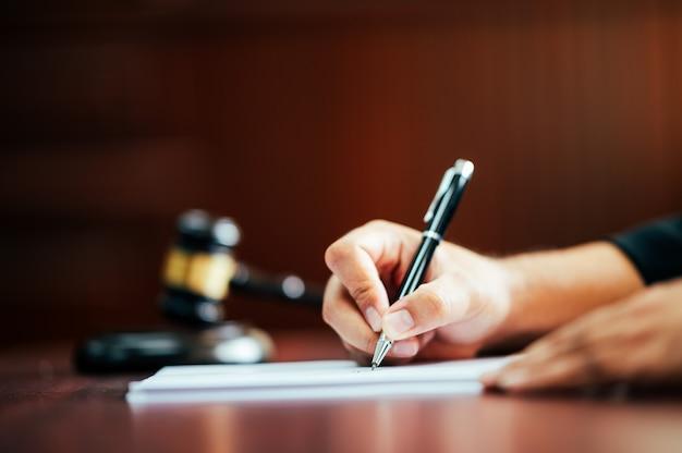 Адвокат, держащий ручку, чтобы писать дела в зале суда