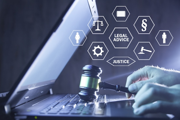 ノートパソコンのキーボードでガベルを保持している弁護士。法的なアドバイス