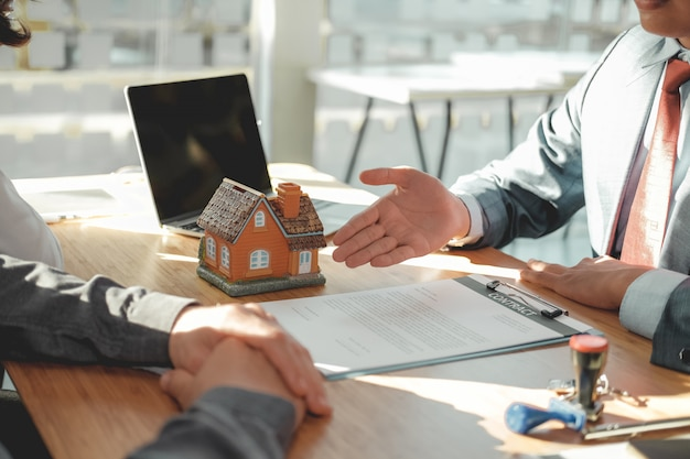 Lawyer insurance broker consulting giving legal advice to couple customer about buying renting house. financial advisor with mortgage loan investment contract. realtor selling real estate