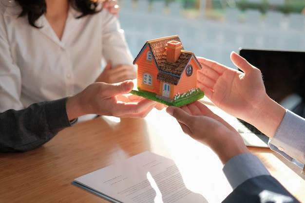 Lawyer insurance broker giving house model to couple customer. realtor selling real estate property. buying renting home concept.