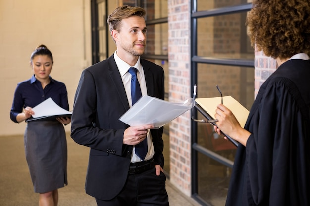 Lawyer looking at documents and interacting with businessman in office
