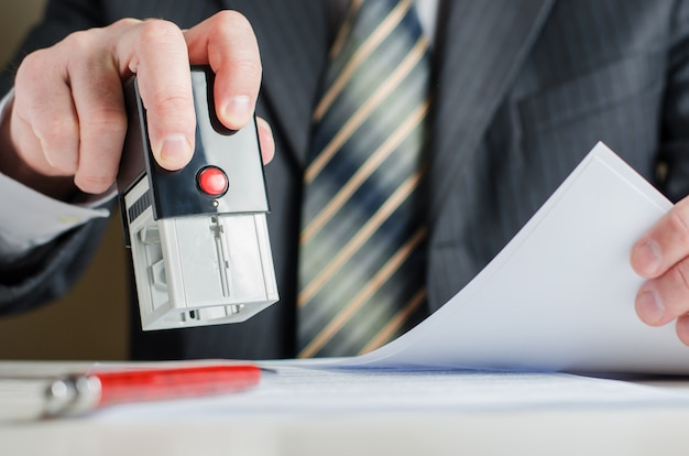A lawyer or notary puts a seal on the document. a stamp in a man's hand.