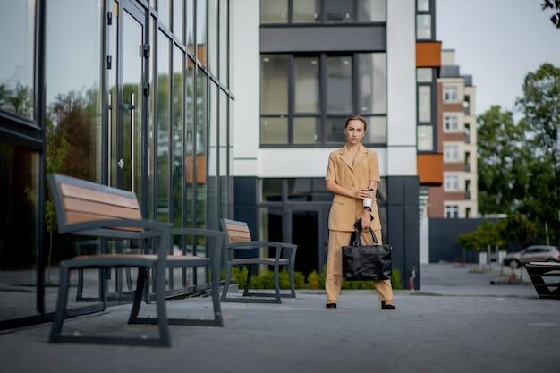 도시 거리에서 일하는 그녀의 방법에 손에 뜨거운 음료 컵을 들고 성공적인 비즈니스 여자의 변호사. 백인 사업가 밖에 서 행복 하 게 웃 고입니다.