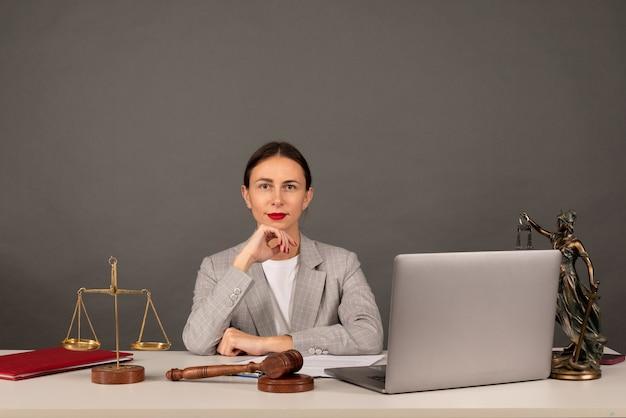 변호사 사무실. 저울과 변호사가 노트북 작업을 하는 정의의 여신상. 법률, 조언 및 정의 개념