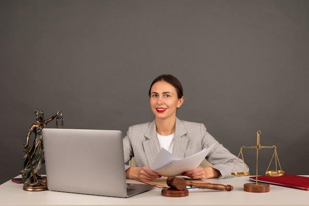Адвокатская контора. статуя правосудия с весами и юристом, работающим на ноутбуке. юридическое право, консультации и концепция правосудия