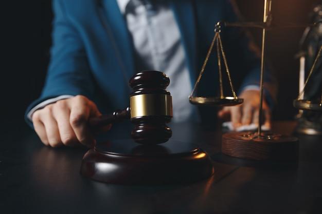 변호사 사무실. 저울과 노트북에서 작업하는 변호사와 정의의 동상. 법률 법률, 조언 및 정의 개념.