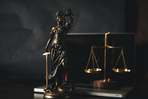 Адвокатская контора. статуя правосудия с весами и юристом, работающим на ноутбуке. юридическое право, консультации и концепция правосудия.
