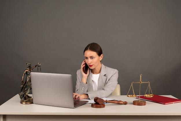 Офис адвоката статуя правосудия с весами и адвокатом, работающим на ноутбуке