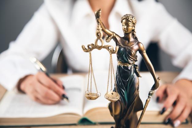 Адвокатская контора. статуя правосудия с весами и работает адвокат
