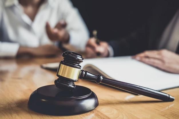 Адвокат или советник, работающий в зале суда, проводят встречи с клиентом, проводят консультации с контрактом