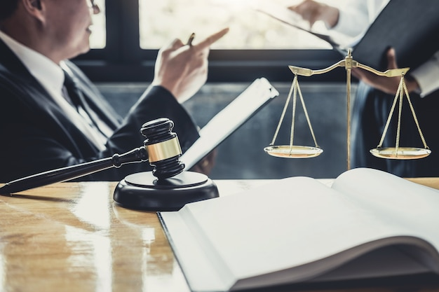 Адвокат или советник, работающий в зале суда, проводят встречу с клиентом, проводят консультации