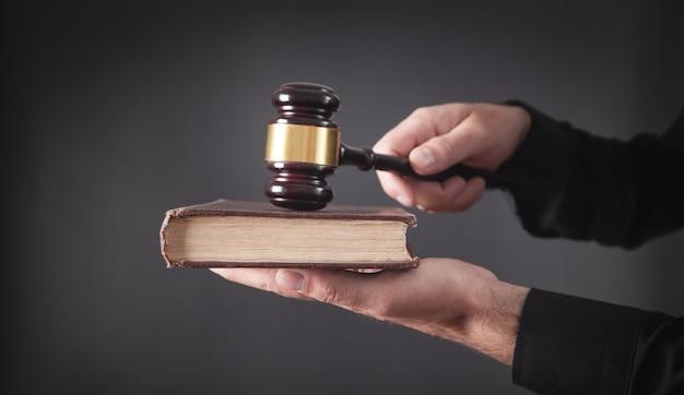 Адвокат или судья с молотком и книгой.