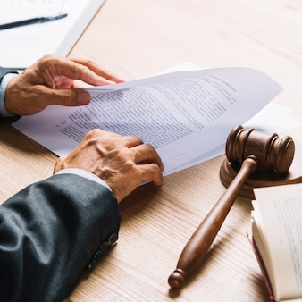 Lawyer's hand holding document with gavel and mallet on wooden desk