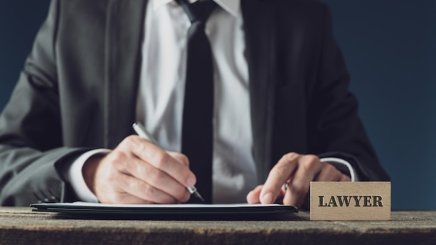 Адвокат сидит за своим деревенским деревянным столом, подписывая юридический документ чернильной ручкой.