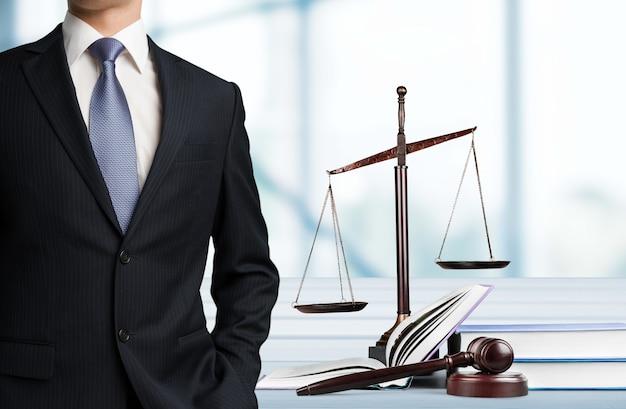 배경에 정의의 저울 근처에 서 있는 변호사