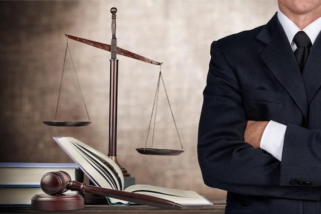 팔짱을 끼고 서 있는 변호사, 배경에 정의의 저울